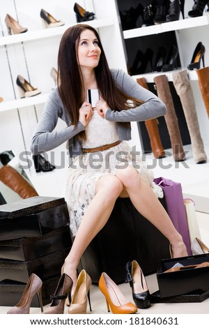 Woman holds credit card in footwear shop sitting on the chair and trying on different pairs of pumps - stock photo