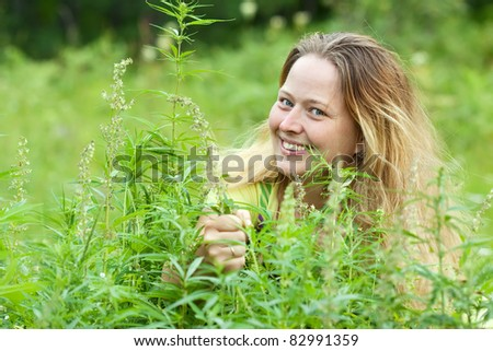 Woman holds fresh hemp  at cannabis plant - stock photo