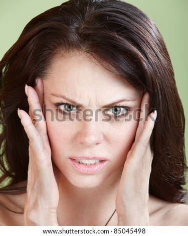 Woman holds head with both hands over green background - stock photo