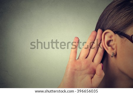 Woman holds her hand near ear and listens carefully isolated on gray wall background  - stock photo