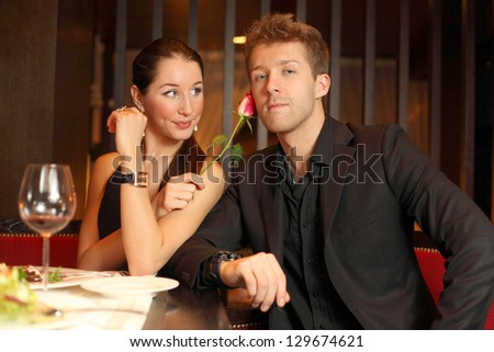 woman holds in her hand a flower and flirting with young man, focus on woman - stock photo