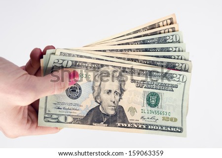 Woman holds out bills twenties tens U.S. currency dollars money - stock photo