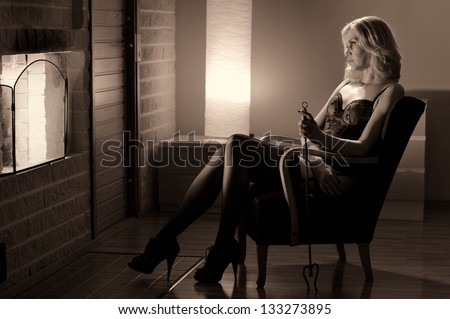 Woman holds poker and sits on the chair, fireplace on the left - stock photo