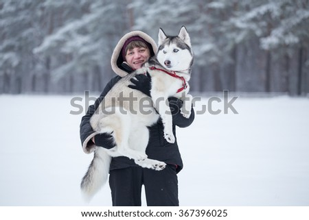 Woman holds Siberian Husky on her arms. Woman and dog are playing in winter park. - stock photo