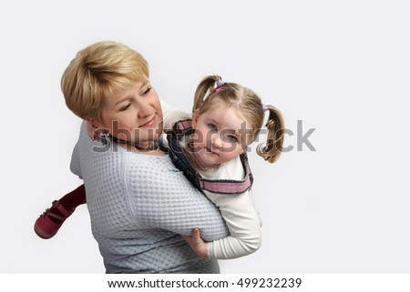 Woman holds small girl on hands - Mother and little girl playing on gray background with copy space