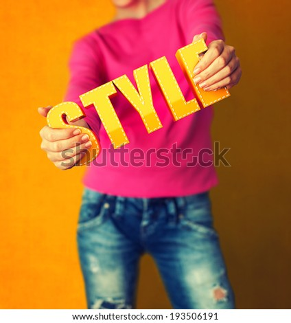 Woman holds word Style on bright colorful background - stock photo