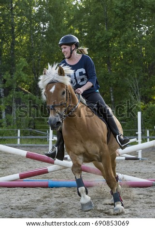 Woman horseback riding and showjumping