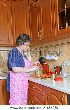 Woman housewife engaged in canning vegetables in the kitchen