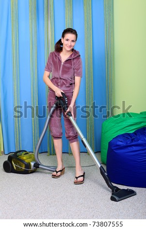 Woman housewife with a vacuum cleaner at home.