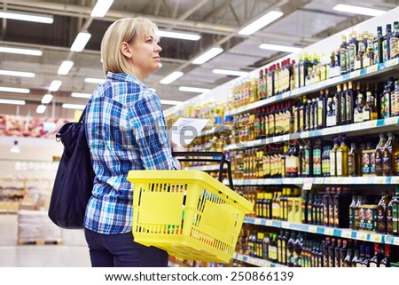 Woman housewife with list shopping in supermarket - stock photo