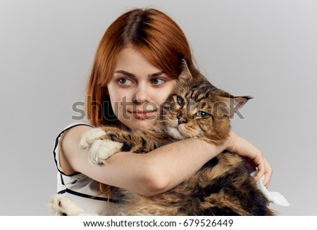 Woman hugging a cat on a light background portrait