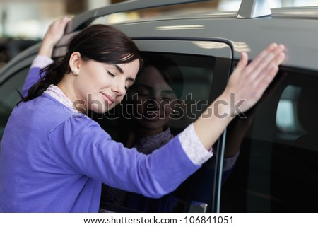 Woman hugging a grey car in a car dealership - stock photo