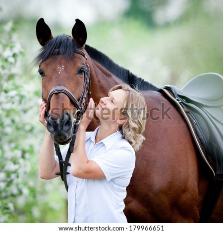 Woman hugging a horse. - stock photo