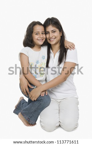 Woman hugging her daughter and smiling - stock photo