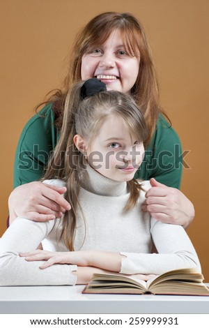 Woman hugging her daughter sitting with a book.  - stock photo