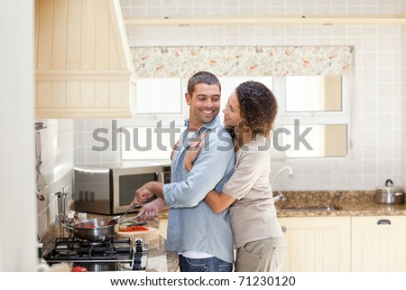 Woman hugging her husband while he is cooking at home - stock photo
