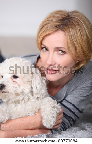 Woman hugging her little white dog - stock photo