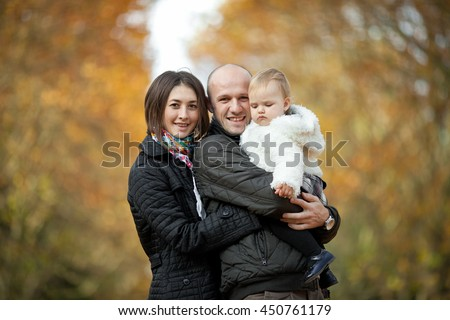 Woman hugs her man while he holds their daughter - stock photo