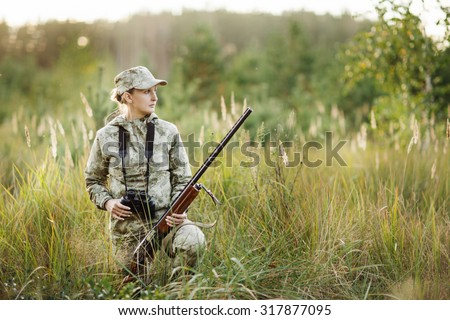 woman hunter with shotgun looking through binoculars in forest - stock photo