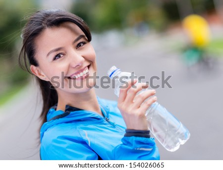Woman hydrating after workout drinking water from a bottle  - stock photo