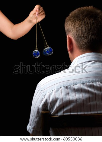 Woman hypnotizes man with a swinging watch during  hypnotic treatment. - stock photo