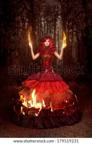 Woman in a beautiful dress on fire - stock photo