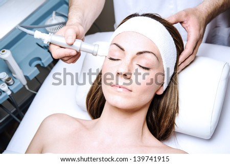 woman in a beauty clinic by becoming a facial