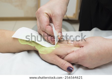 Woman in a beauty salon doing depilation - stock photo