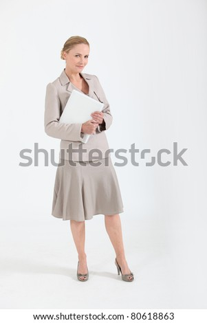 Woman in a beige skirt suit with a folder - stock photo