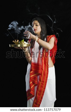 Woman in a Bengali sari holding pooja thali - stock photo