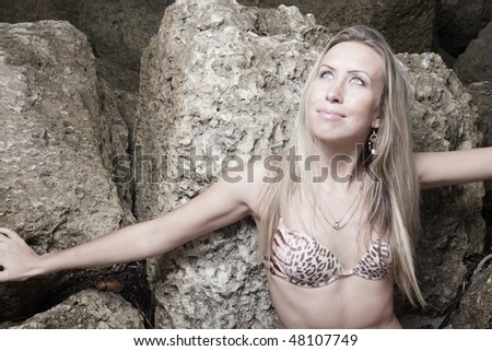 Woman in a bikini by the rocks