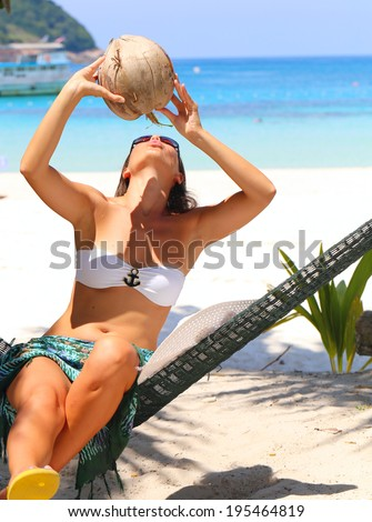 woman in a bikini reclining in a hammock drink the coconut juice - stock photo