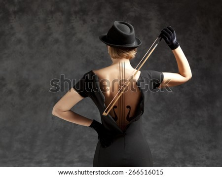 Woman in a black dress and black hat plays the violin. Photo compilation, photo and hand-drawing elements combined - stock photo