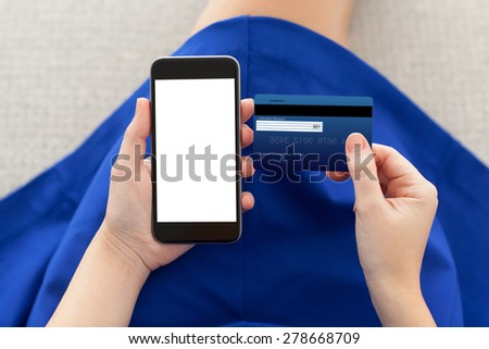 woman in a blue dress holding a phone with isolated screen and credit card - stock photo