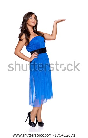 woman in a blue dress  holding blank copy space on her open palm, over white background - stock photo