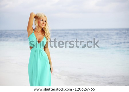 woman in a blue dress on the ocean coast - stock photo