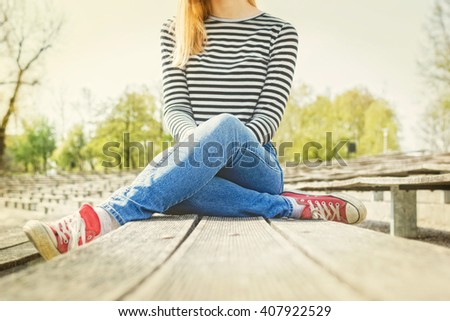 Woman in a blue jeans, striped t-shirt and  red canvas sneakers on her feet, sitting on a bench, legs crossed. Bright and sunny day. - stock photo