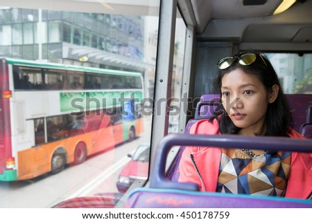 Woman in a bus looking out the window at traffic in city. Asian tourists traveling on the trip. Passenger double-decker bus.