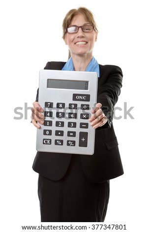 Woman in a business suit and a blue blouse, holding a large calculator infront of her.
