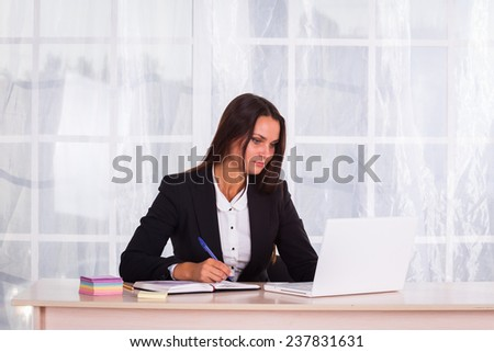 Woman in a business suit. Business woman sitting at the table, working with the computer. Business, work, business woman - business concept girl. The idea about the woman's business.