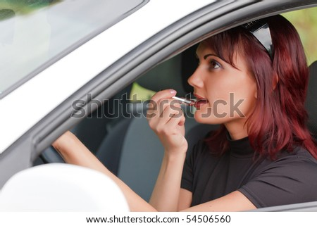 Woman in a car doing makeup.