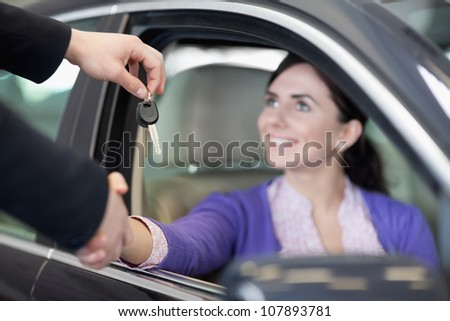 Woman in a car while shaking a hand and receiving car keys in a car dealership