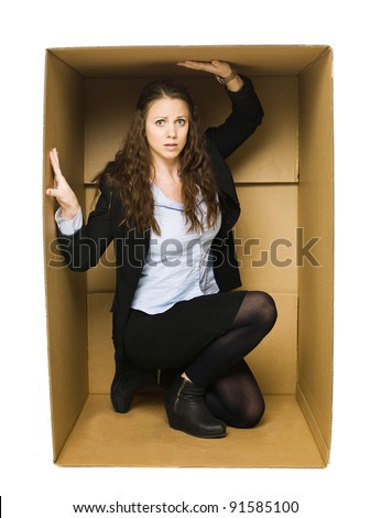 Woman in a cardboard box isolated on white background