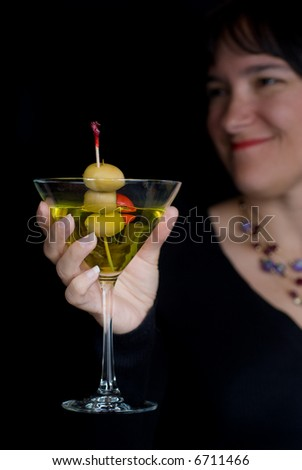 Woman in a celebration setting shows her martini cocktail against a moody black background - stock photo