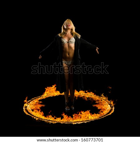 Woman in a circle of fire Blazing flames over black background - stock photo