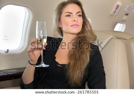woman in a corporate jet drinking a glass of champagne - stock photo