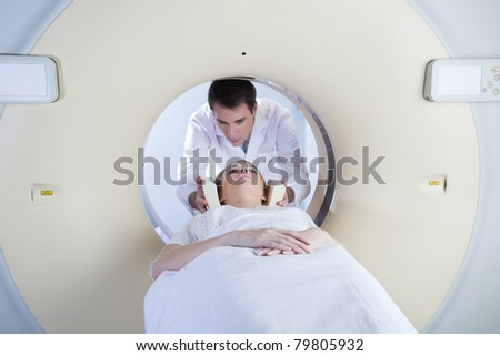 woman in a ct scan with medical professional - stock photo