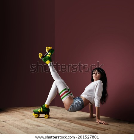 woman in a dark room posing in a roller skates - stock photo
