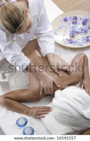 Woman in a day spa getting a deep tissue massage therapy - stock photo