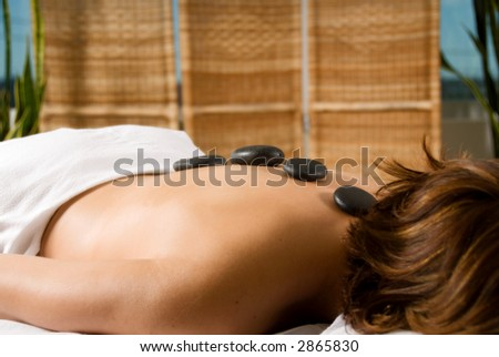 woman in a day spa with hot stones on her back - stock photo